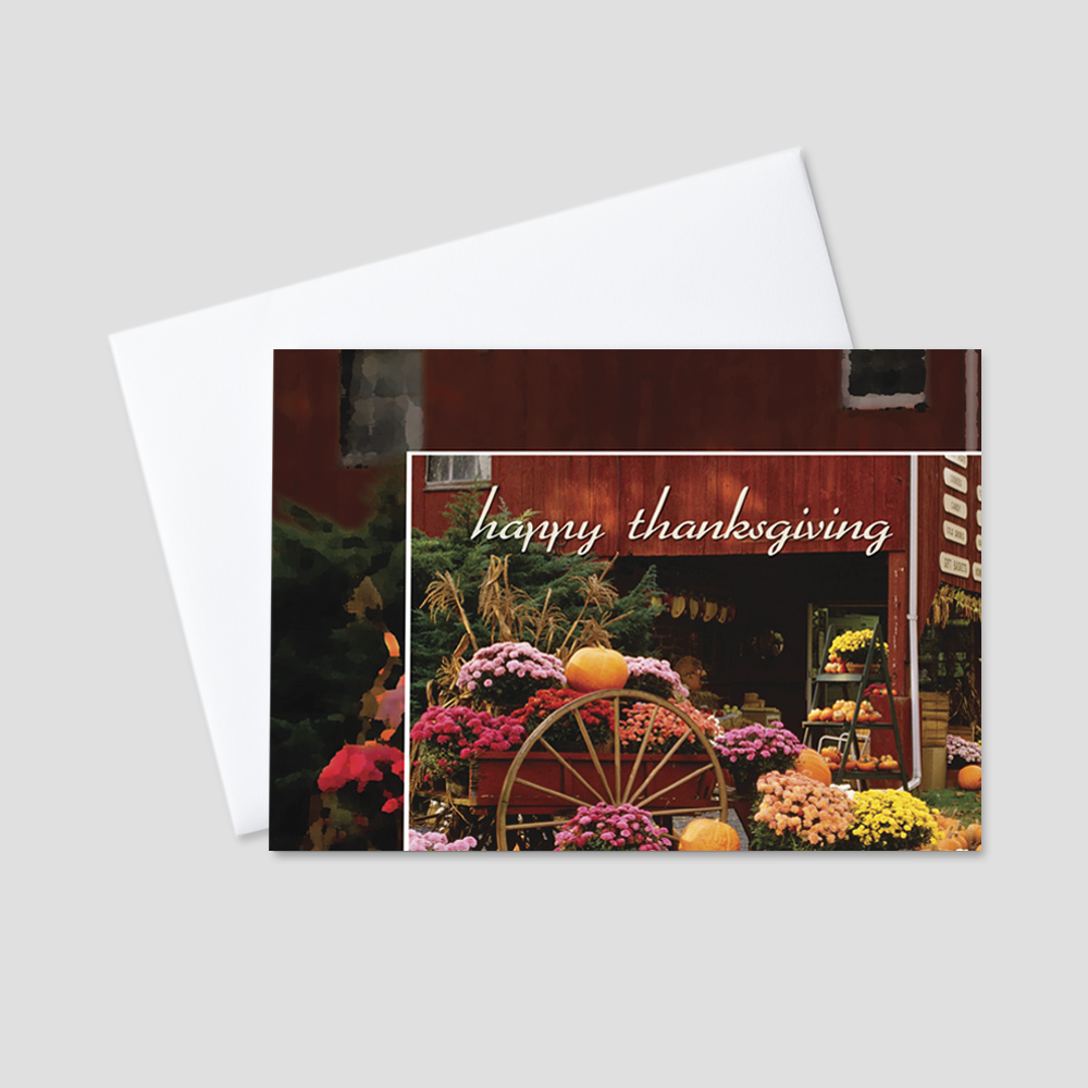 Festive Thanksgiving greeting card featuring an autumn display of a wagon filled with pumpkins and flowers next to a red barn
