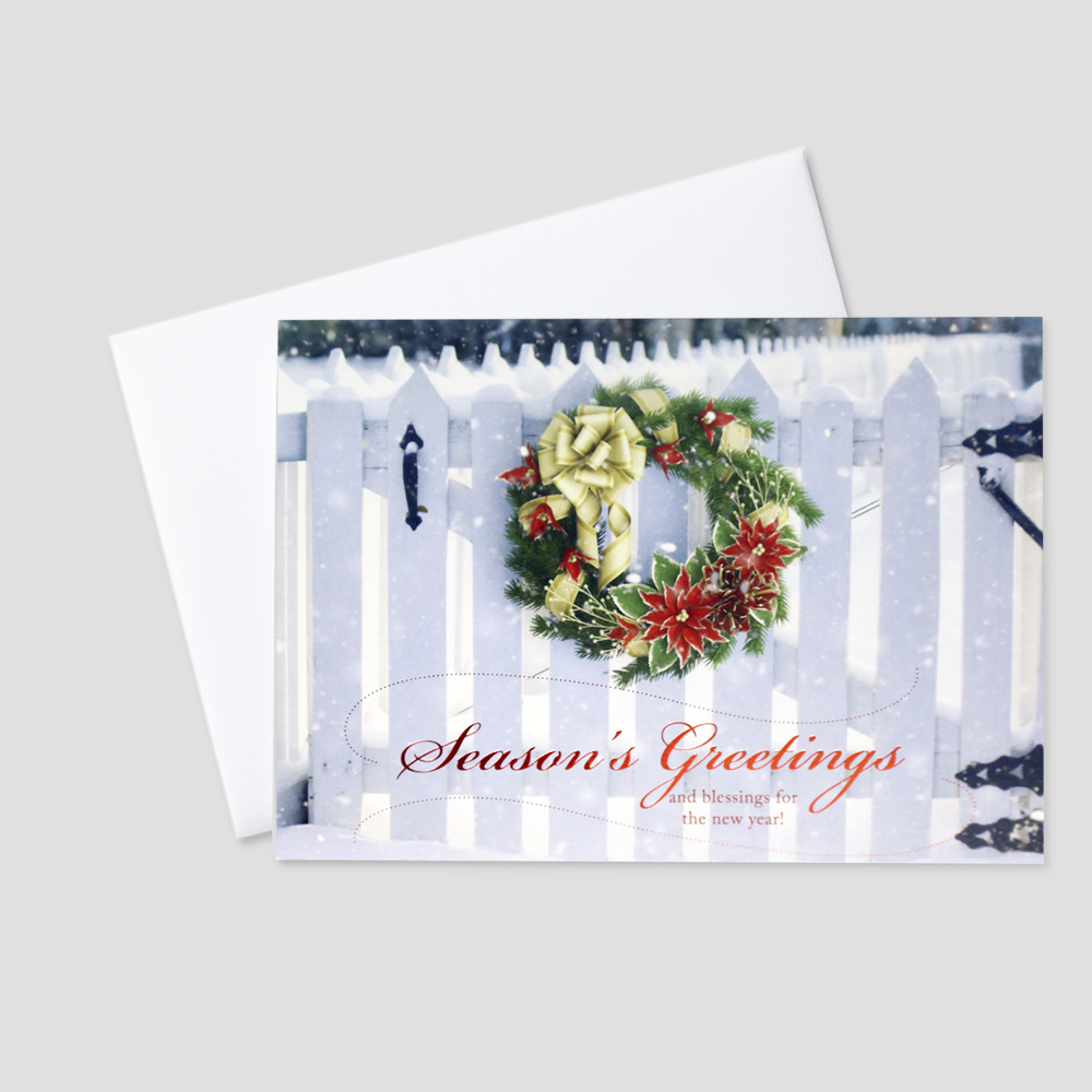 Professional Holiday greeting card with a holiday wreath on a white picket fence and a Season's Greetings message in red foil print