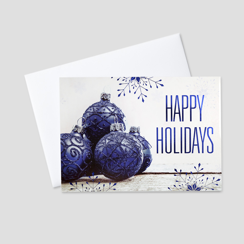Business Holiday greeting card featuring glimmering blue ornaments and blue foil printed snowflakes and Happy Holidays message