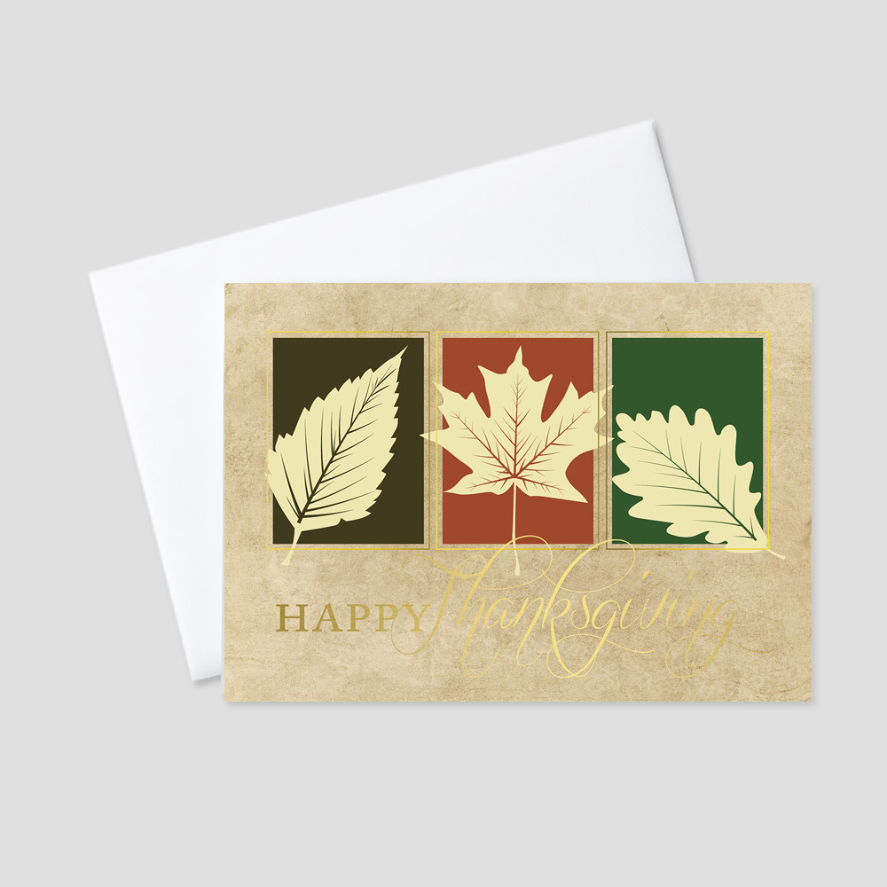 Business foil printed Thanksgiving card featuring a tan parchment colored background and fall-colored leaves with a gold foil Happy Thanksgiving script message
