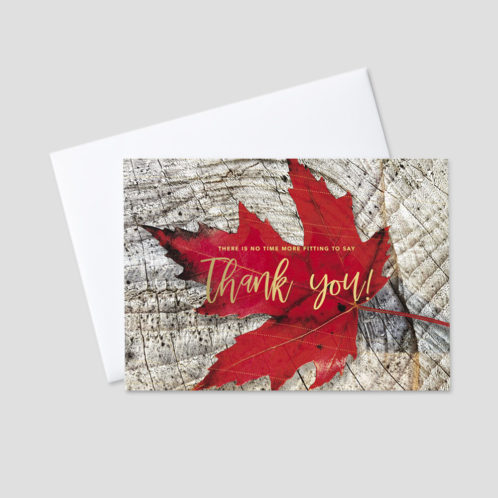 Company foil printed Thanksgiving greeting card featuring a rustic tree background and a red maple leaf with a gold foil printed business Thanksgiving message