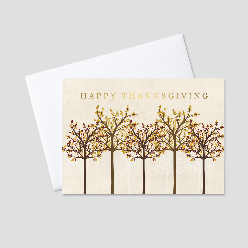 Corporate foil printed Thanksgiving card with a tan background, silhouettes of the foreground trees in the background and autumnal colored trees below a gold foil printed Happy Thanksgiving message
