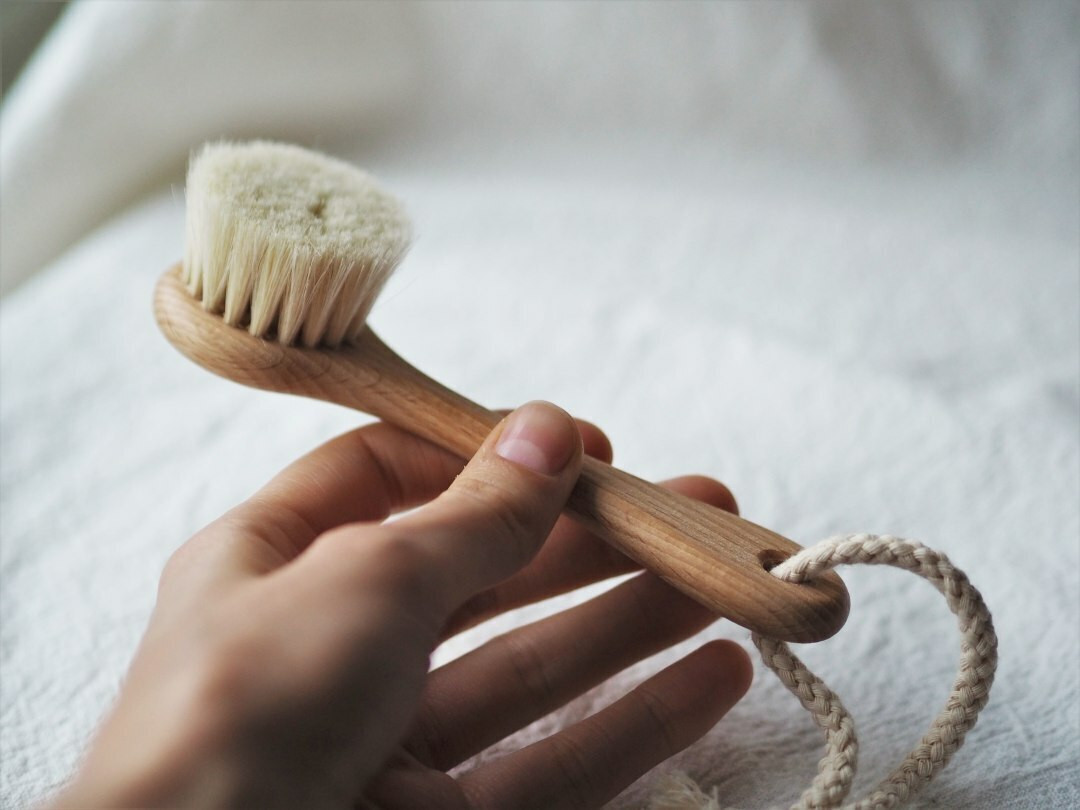 Face brush with handle and strap