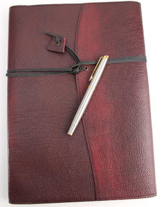 Ruby Leather Book Wrap. Handmade in Australia. Kangaroo leather wrapping strap keeps books and papers securely inside. Pen not included - for scale only.