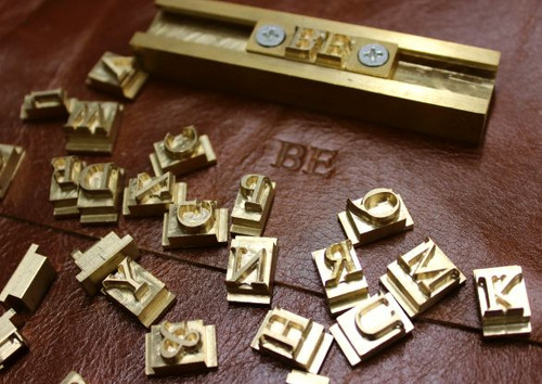 The beautiful brass letters and block used for monogramming leather items.