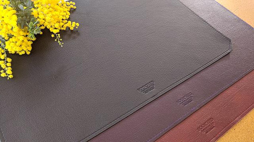 Variation in size.  Large desk mats shown here in Violet Purple and Scarlet Red with a Regular sized black desk mat on top.