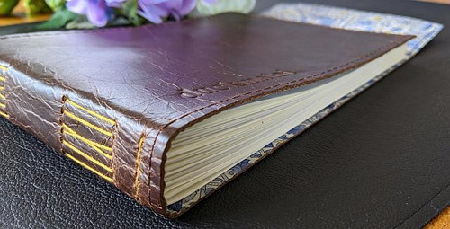 Guest Book in Antique Oak Leather and lined with Liberty of London Fabric.