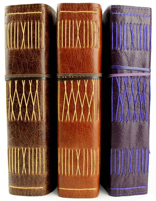 Majestic sized A5 leather journals. Hand stitched and handcrafted in Australia. The leathers featured here are: Antique Oak, Cognac and Violet Purple.