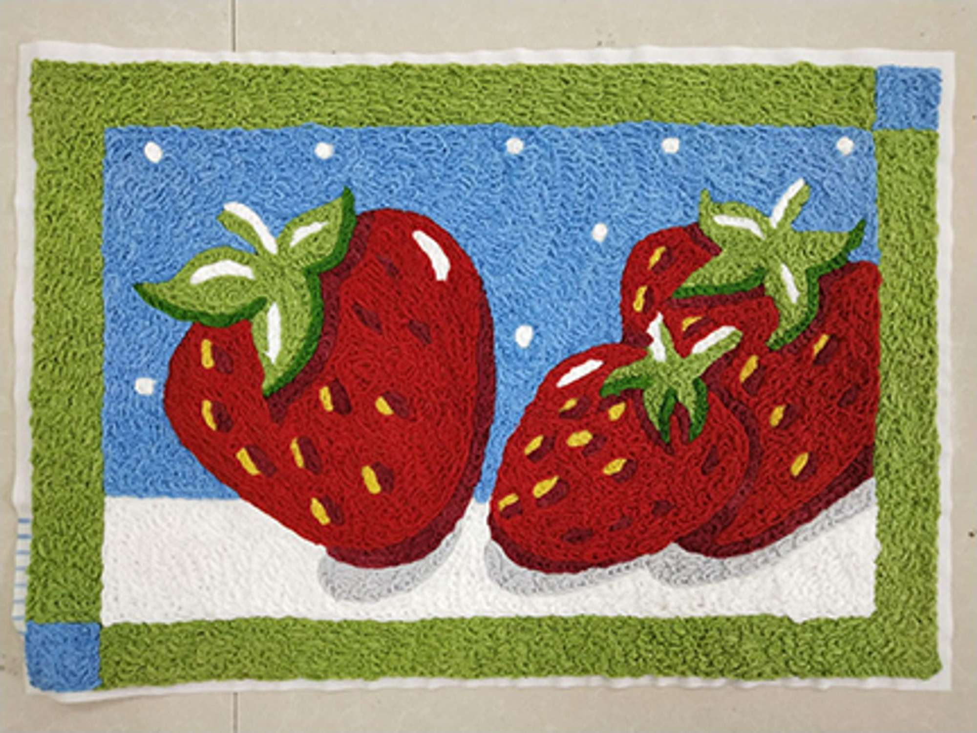 Three tantalizingly red strawberries act as the focal point for this Jellybean® accent rug by Diedre Mosher. Subdued hues of sky blue and light green frame the borders making the fruit appear all the more inviting. Machine washable durability make this accent rug suitable for indoor and outdoor use.