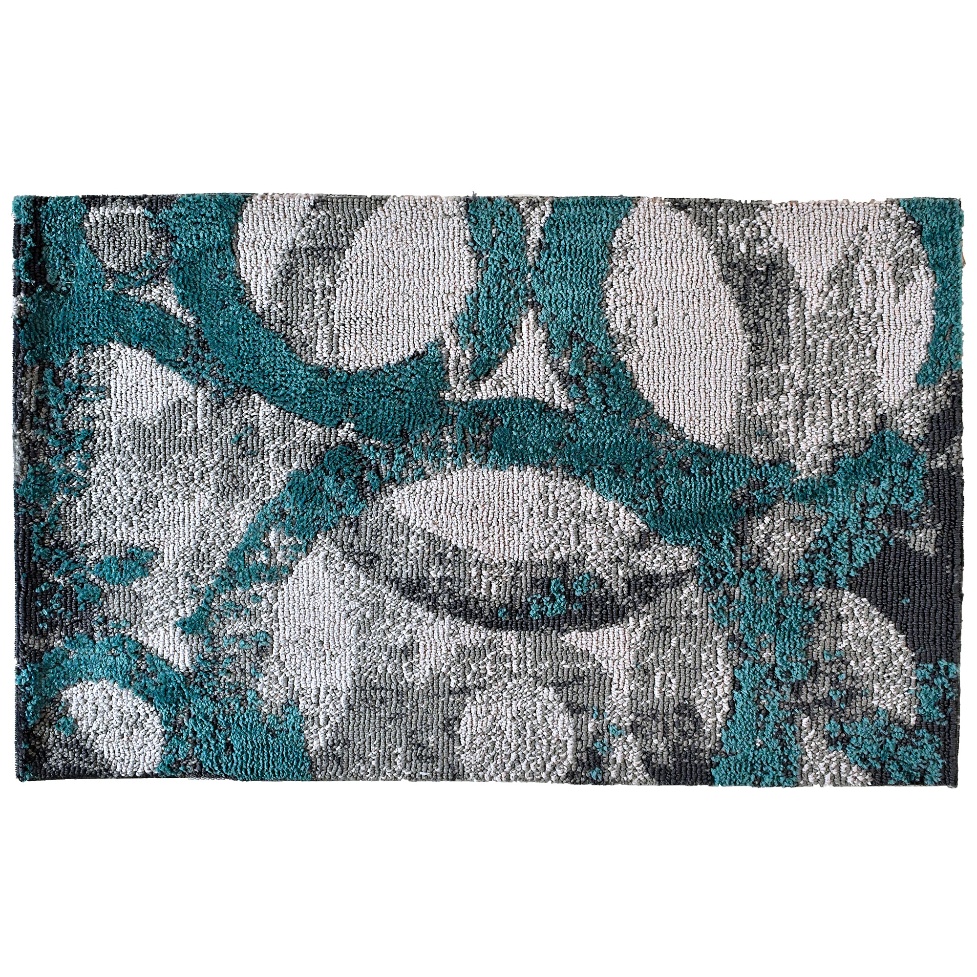 Rings of teal and gray intertwine on this Simple Spaces by Jellybean® accent rug. Artist Michael Mullan's selection of two complementary colors on a layered, intricate design will bring depth to your room. This accent rug is available in two sizes for additional placement options.