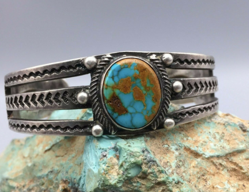 Hand stamped Fred Harvey  era cuff, with a turquoise stone that has a lovely tan/brown matrix.