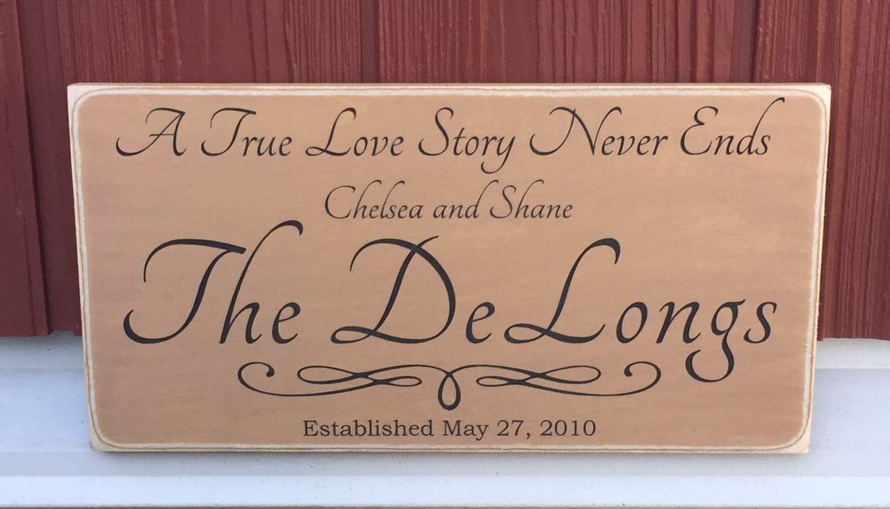 A True Love Story Never Ends Family Sign - golden brown background with black text