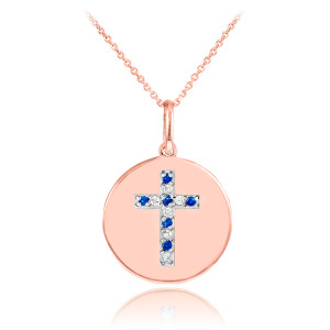 Cross disc pendant necklace with diamonds and sapphire in 14k rose gold.