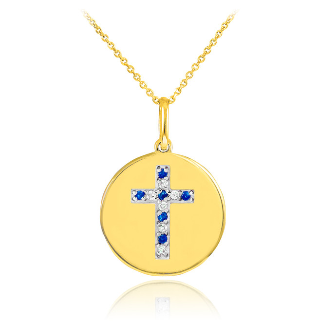 Cross disc pendant necklace with diamonds and sapphire in 14k gold.