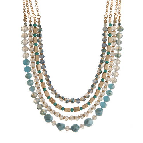 "Gold tone layering necklace displaying strands of turquoise and blue glass beads. Approximately 18"" in length."
