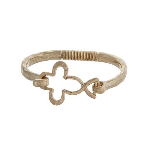 Worn gold tone latch bangle bracelet with an open quatrefoil.