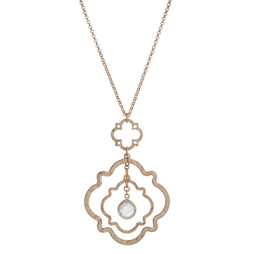 """Worn gold tone layering linked quatrefoil with a dangling clear glass stone. Approximately 30"""" in length."""
