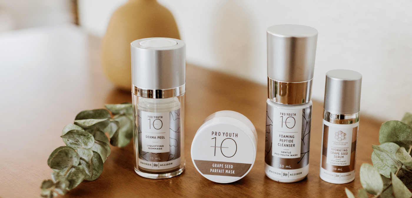 A stylized photo of four Rhonda Allison skincare products from the -10 Pro Youth line. There are some leaves and a ceramic vase for decoration.