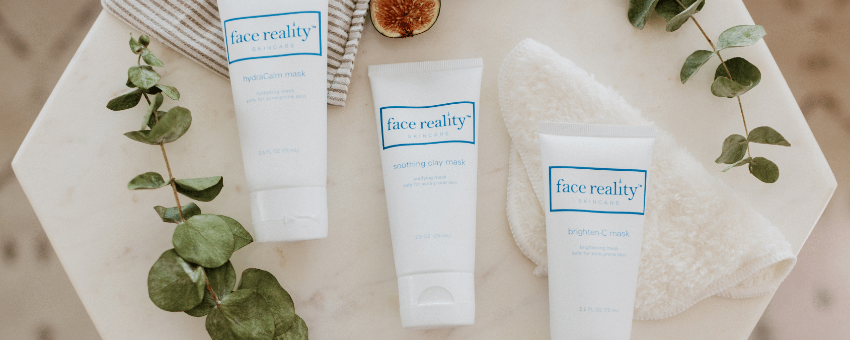 Three acne-safe Face Reality masks on a marble table with a fig and a towel.