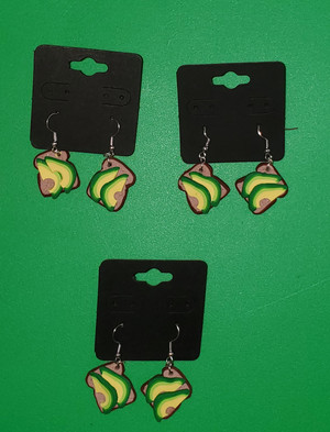 Photograph showing the Polymer Clay Avocado Toast Earrings. Clay avocado slices are fanned across two slices of bread.