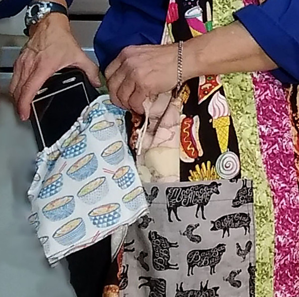 The placement of a cell phone into the Drawstring Pocket. The pouch or pocket is then placed behind the apron surface to protect the items in the bag.