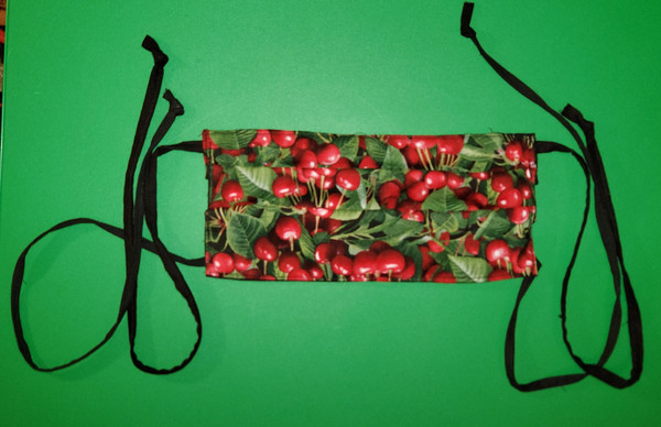 Cherries and leaves on a face mask.