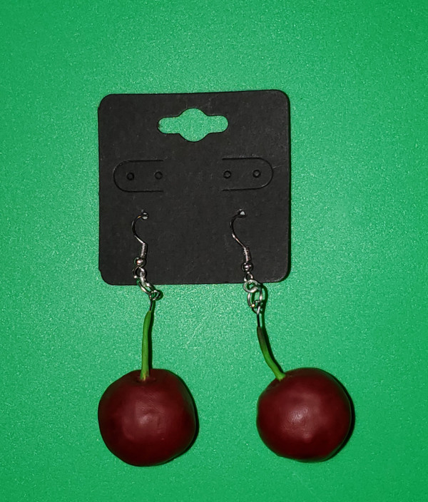 Polymer clay earrings that are hand sculpted to look like fresh, ripe cherries.