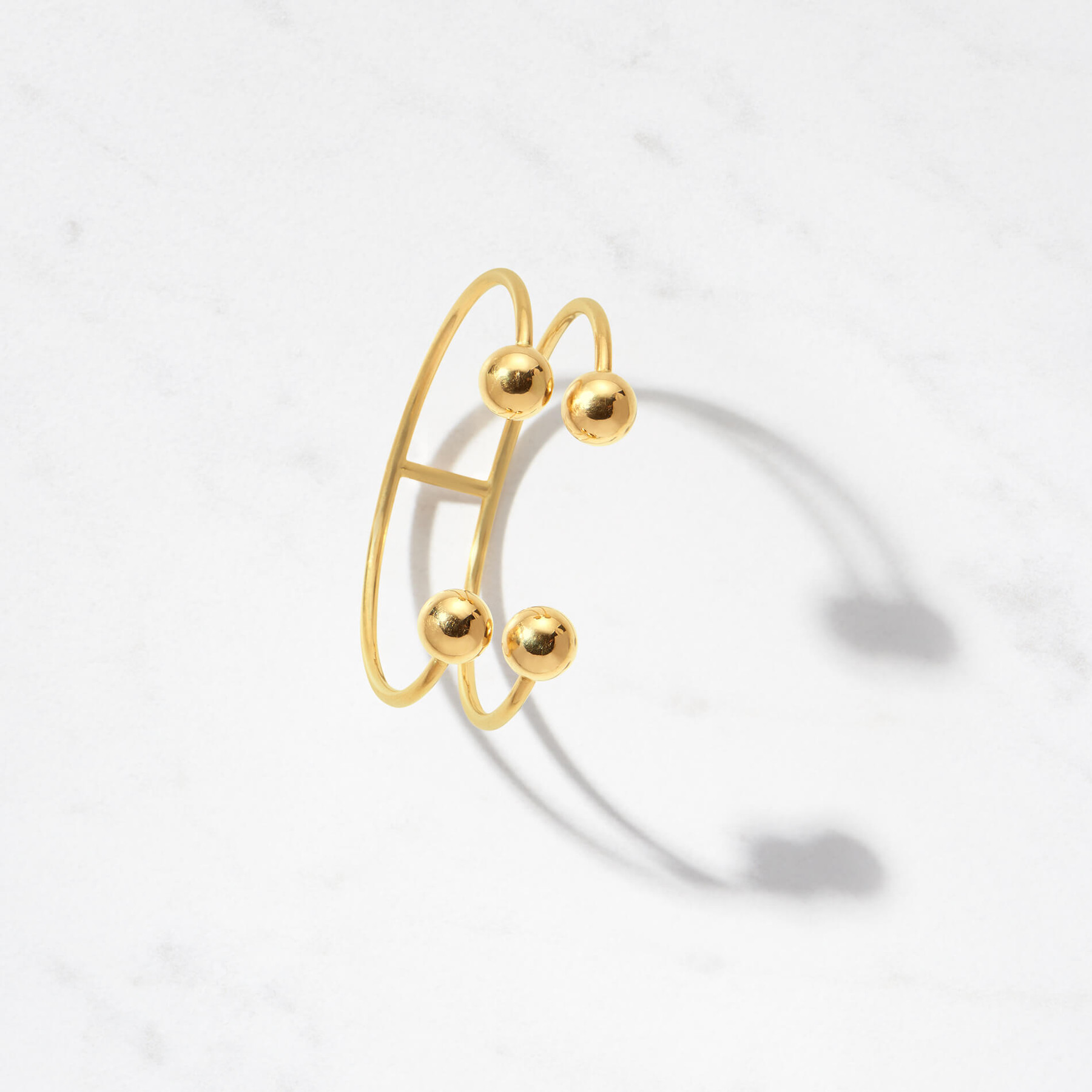 Golden orbs align two perfectly formed arcs on our Astra II Cuff in 22 karat polished gold with a gold weight of approximately 32 grams.