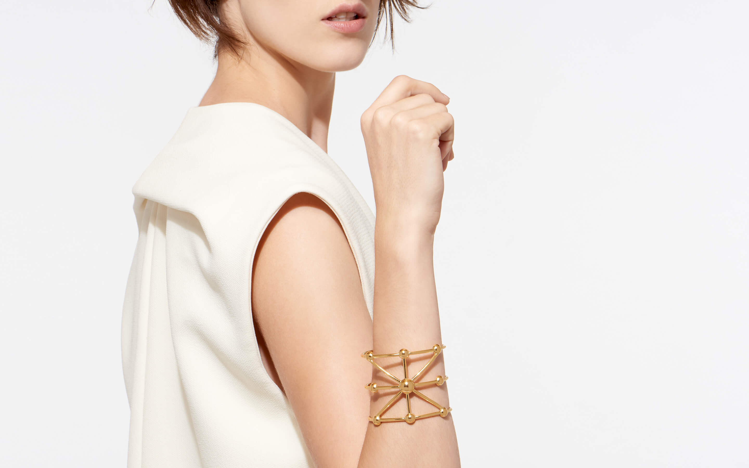 lissome model showcasing 22 karat gold cuff with globes in stellar shape