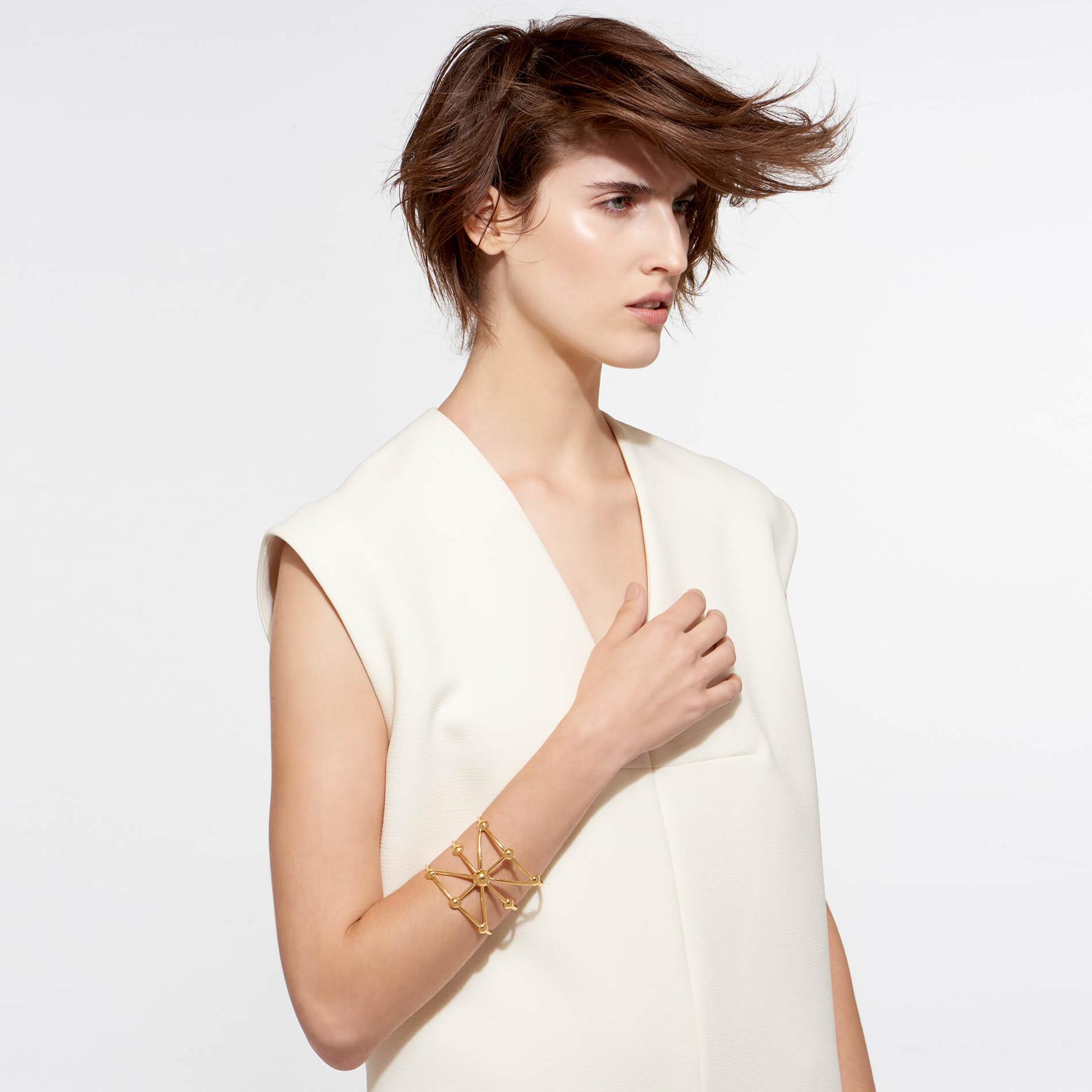 beautiful model wearing 22 karat gold wrist cuff in galactic design