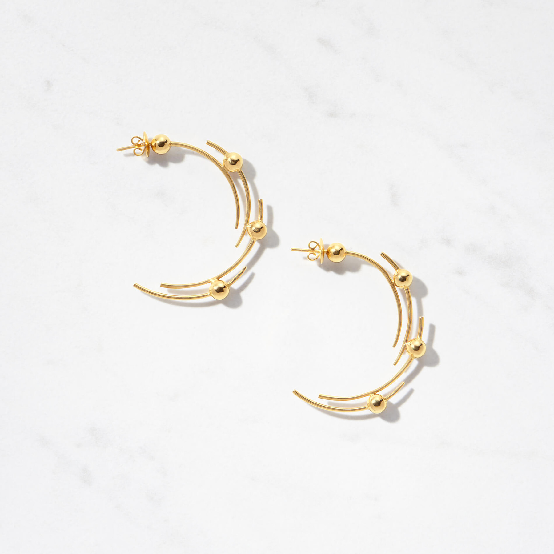 Floating arcs collide with multiple golden moons to create our Carina Earrings. Handcrafted from 22 karat gold and possessing a gold weight of approximately 16 grams, Carina is inspired by the Carina Constellation in the Southern skies.
