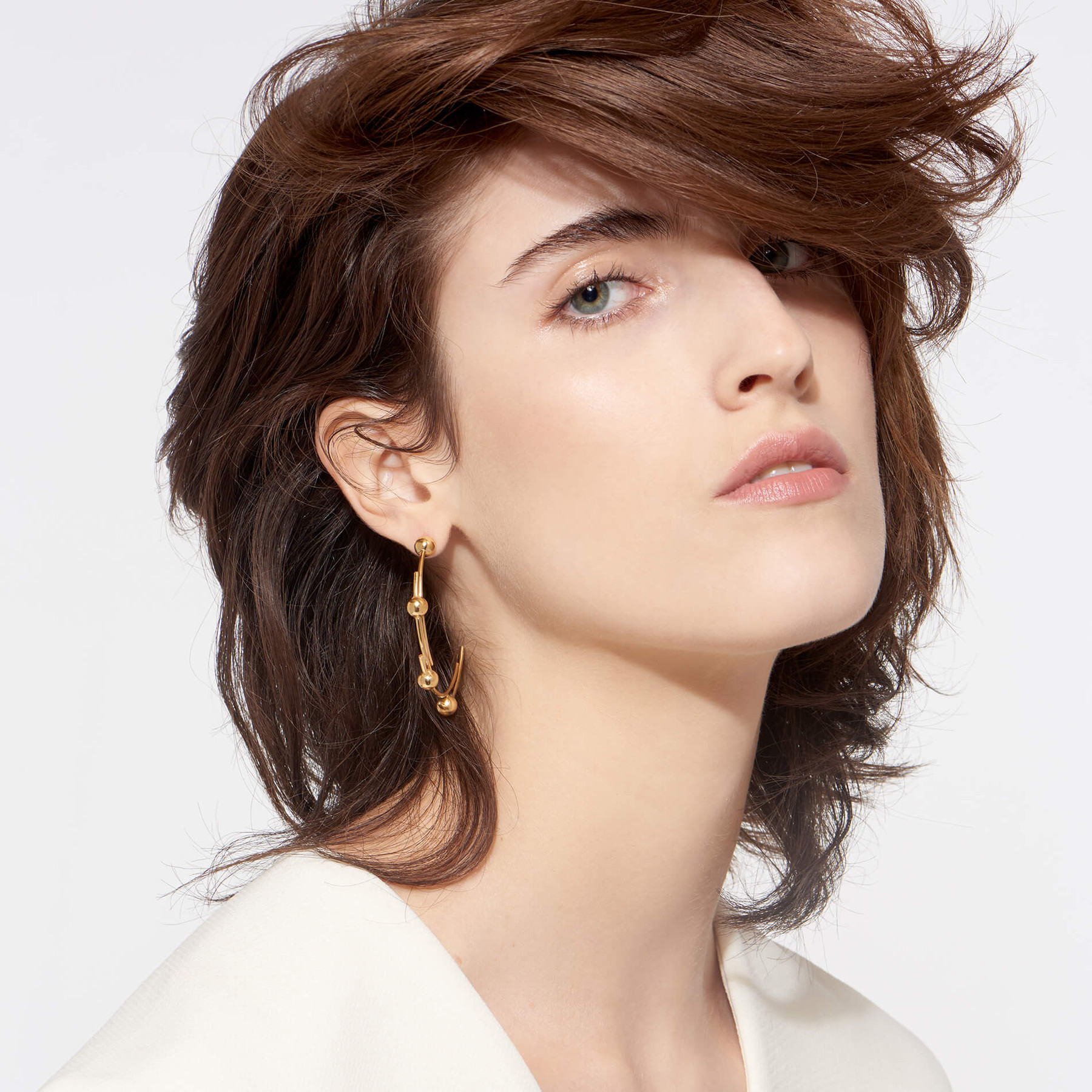 glowing 22 karat gold earrings in contemporary design with multiple spheres displayed on attractive model