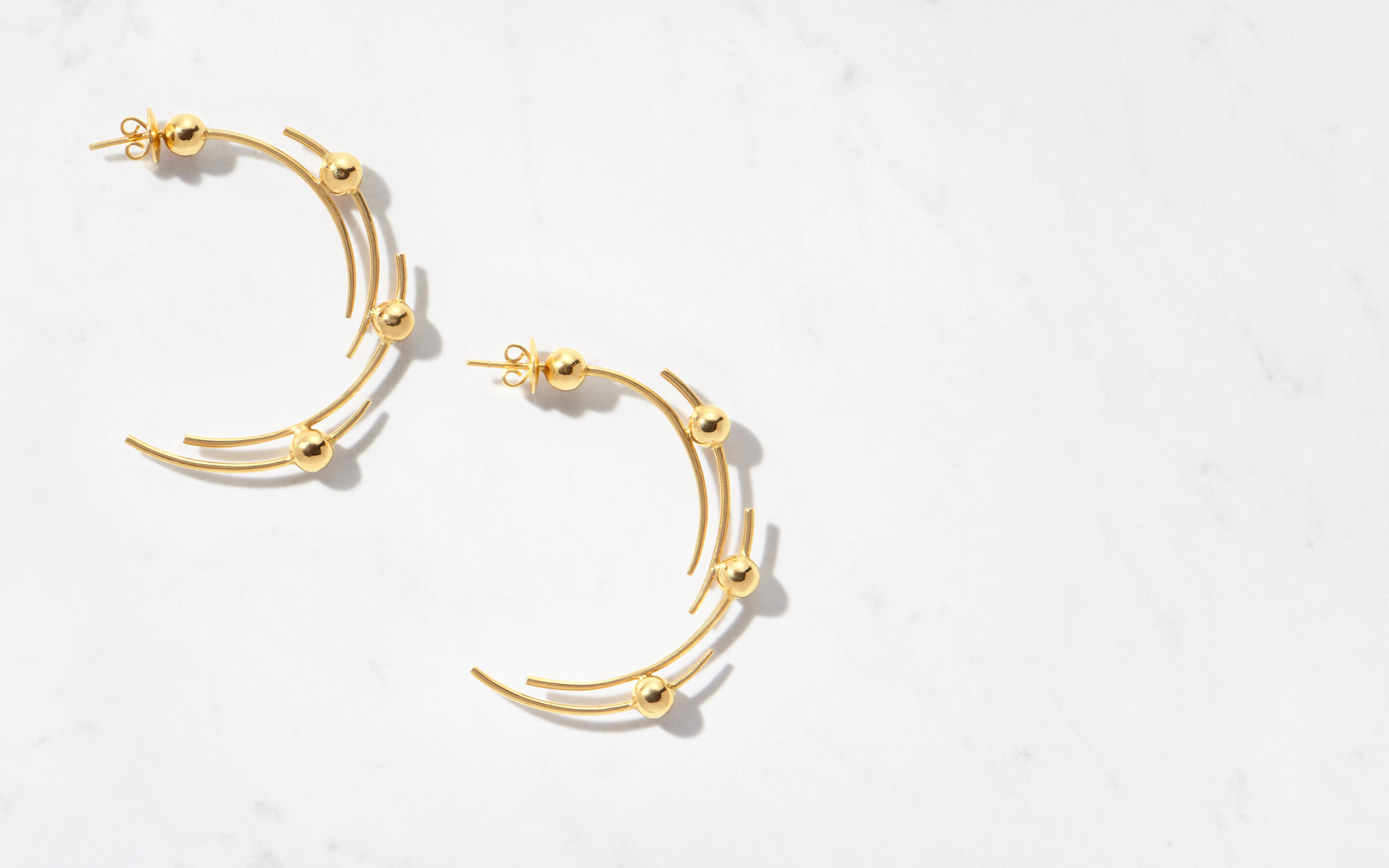 luxurious 22 karat gold earrings made of multiple curves and globes