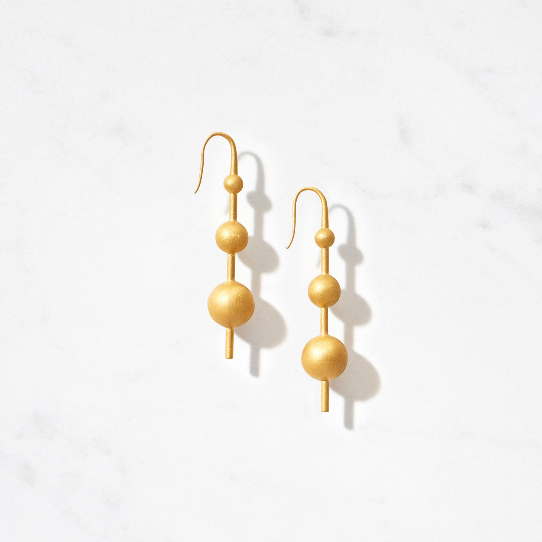 Our Luna Aurelia Earrings boast three golden moons floating on a vertical axis. Handcrafted from 22 karat matte gold with a gold weight of approximately 14 grams.