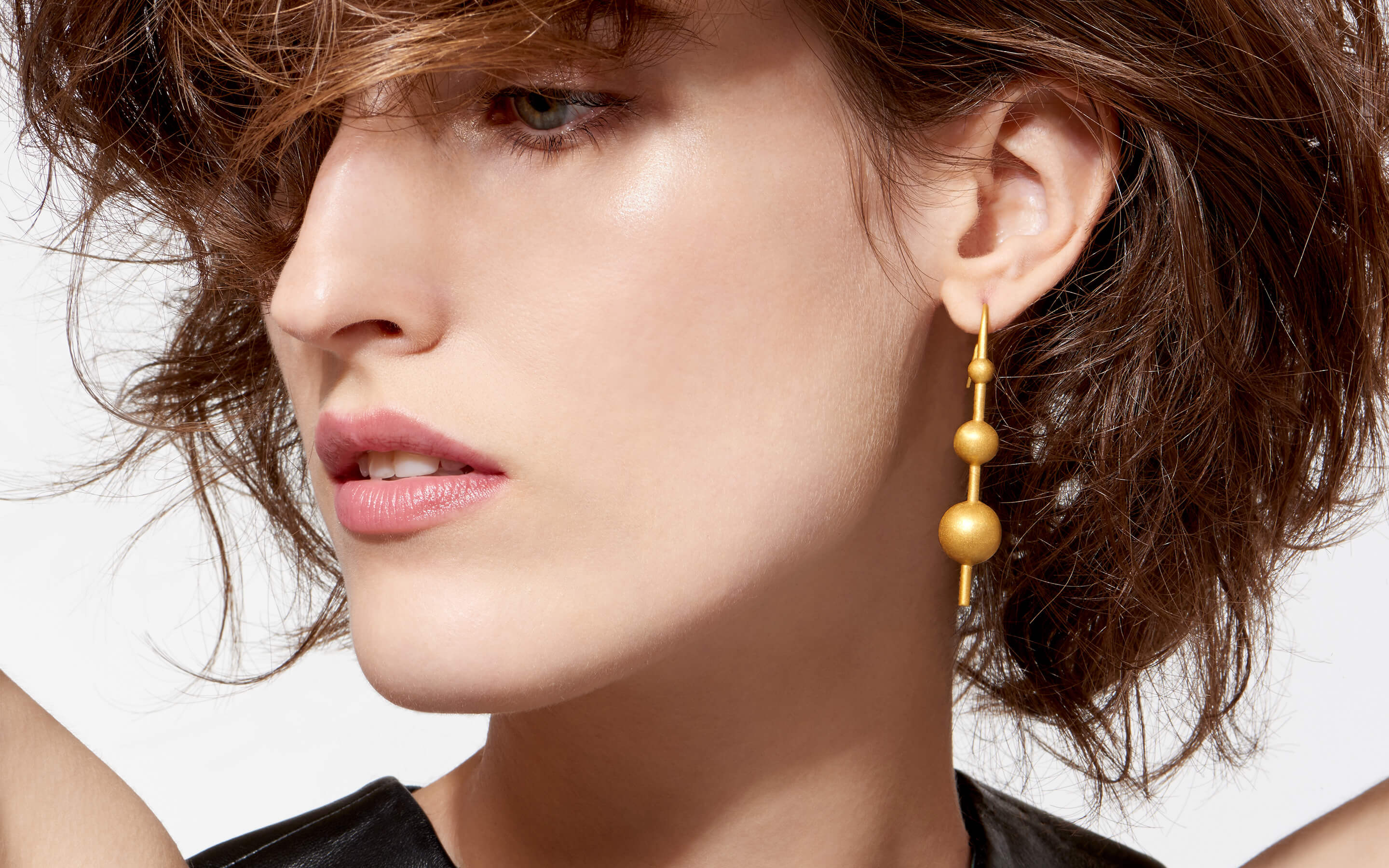 white female model gazing pensively graced with 22 karat gold post earrings containing three globes