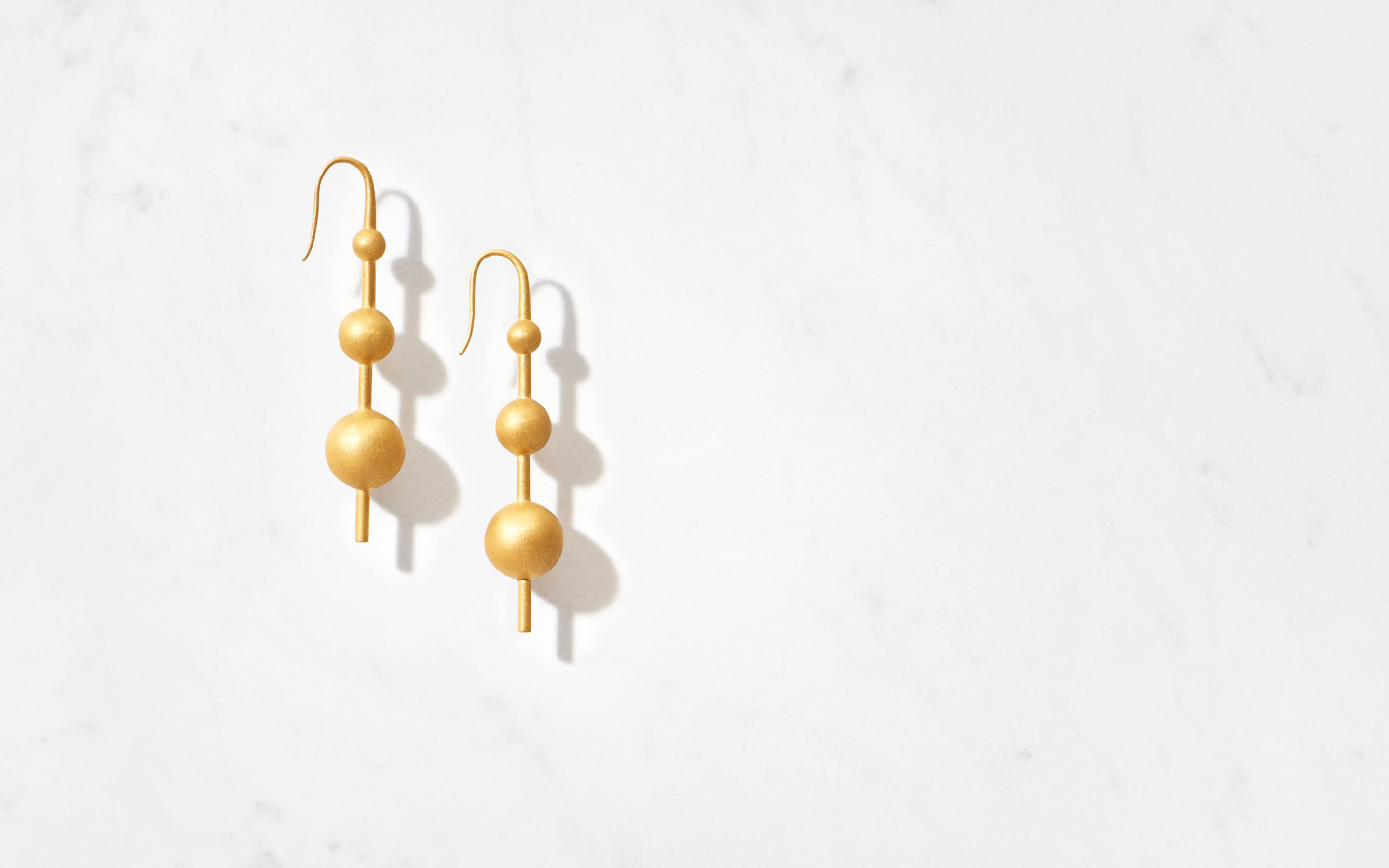 stylish 22 karat gold post earrings with three gradated globes in matte finish