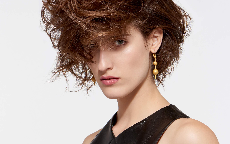 burnished 22 karat gold post style earrings with three spheres showcased on glamorous model