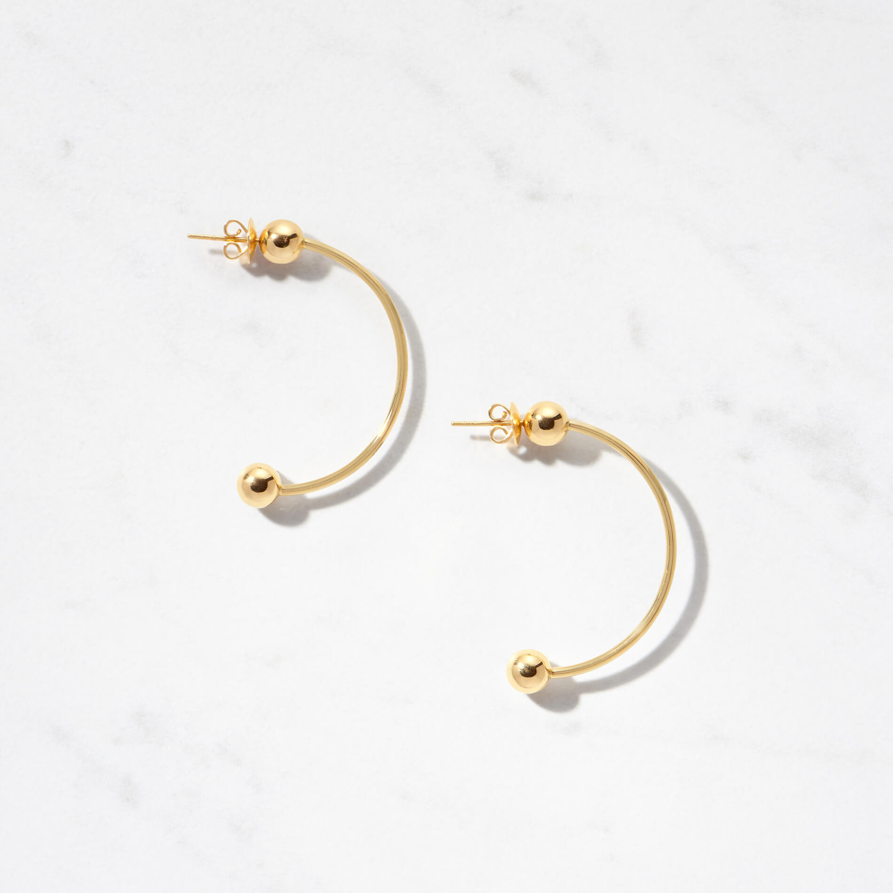 Two golden moons grace the ends of an arc to create our Celestia II Earrings. With a gold weight of about 15 grams, Celestia II is handcrafted from 22 karat polished gold.