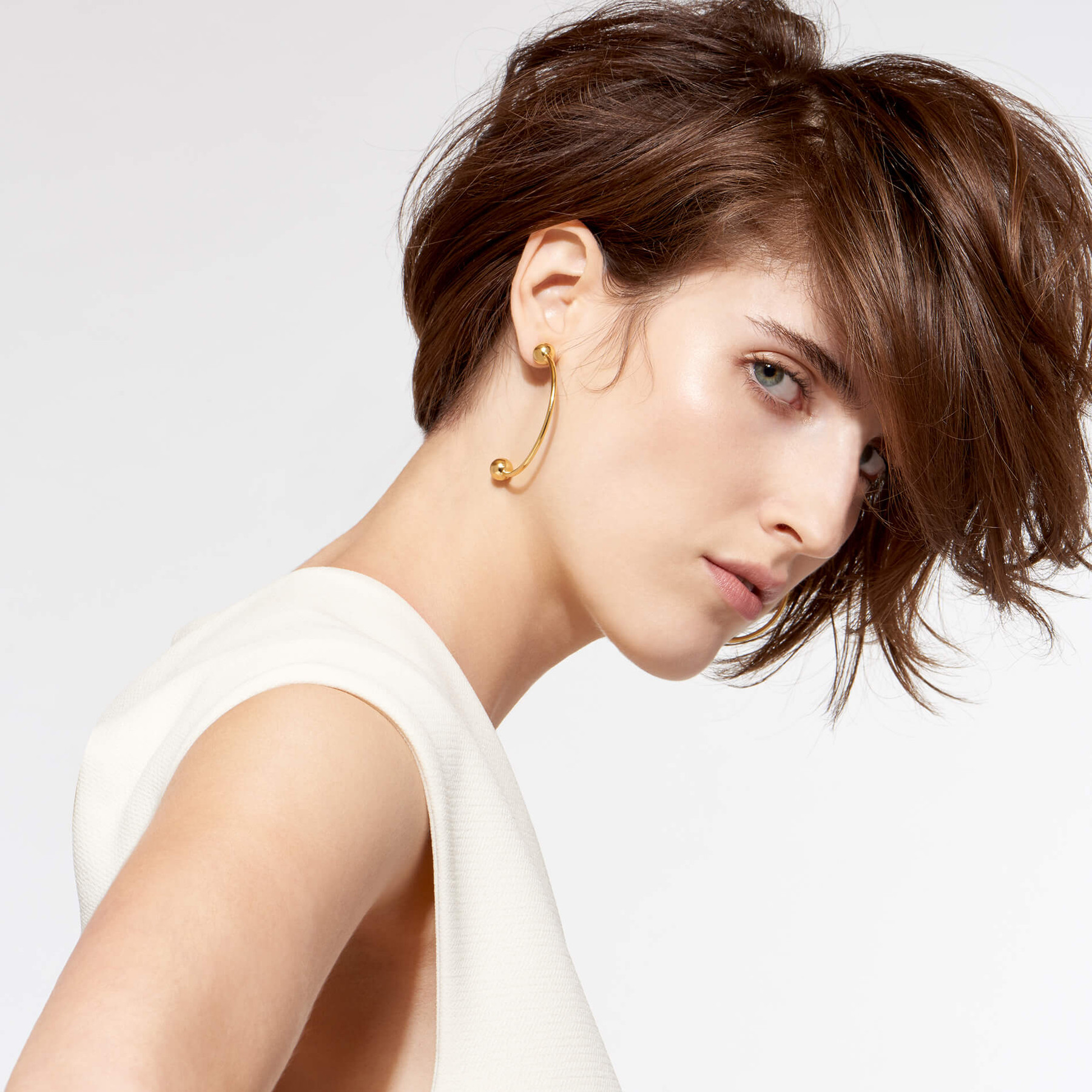 glimmering 22 karat gold curved earrings with globes on stunning white woman