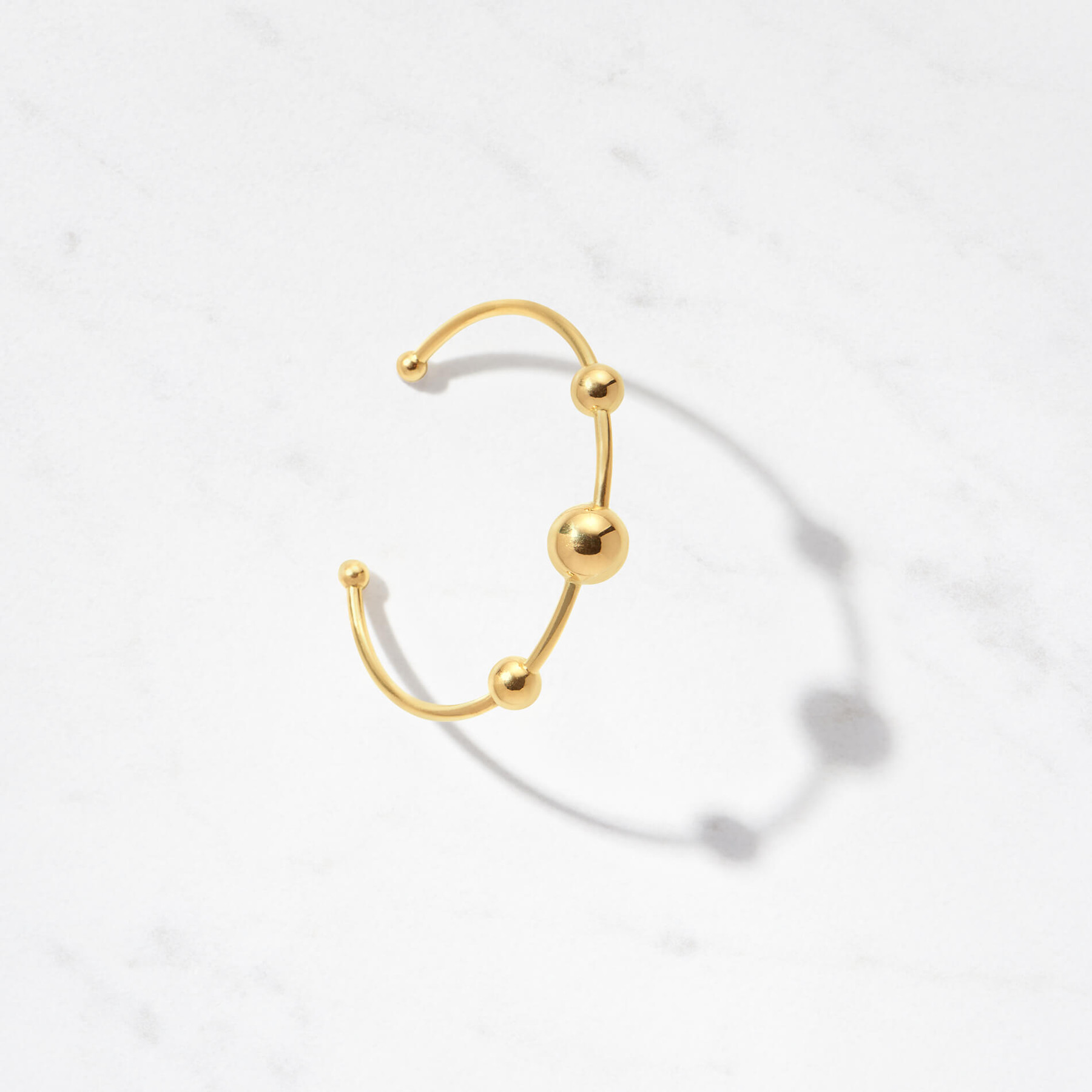 Multiple golden moons orbit your wrist. Our Astra I Cuff, with a gold weight of approximately 15 grams, shines in 22 karat polished gold.