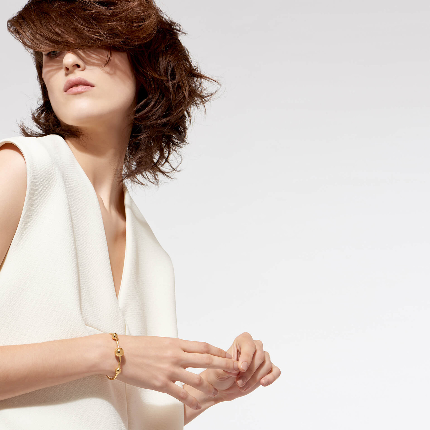 redheaded model wearing 22 karat gold wrist cuff with multiple spheres