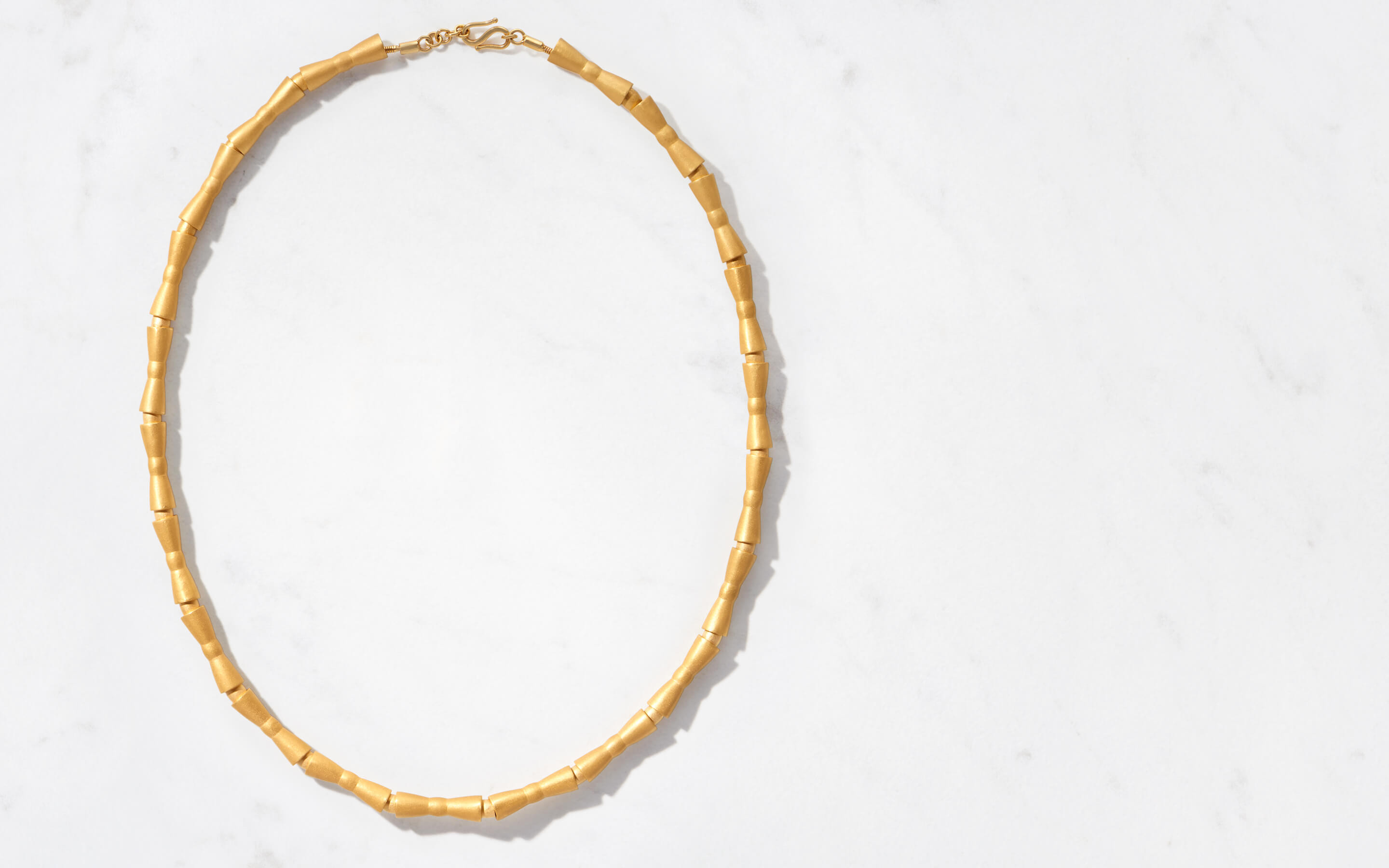 22 karat gold choker necklace with bowties rendered in modern beads
