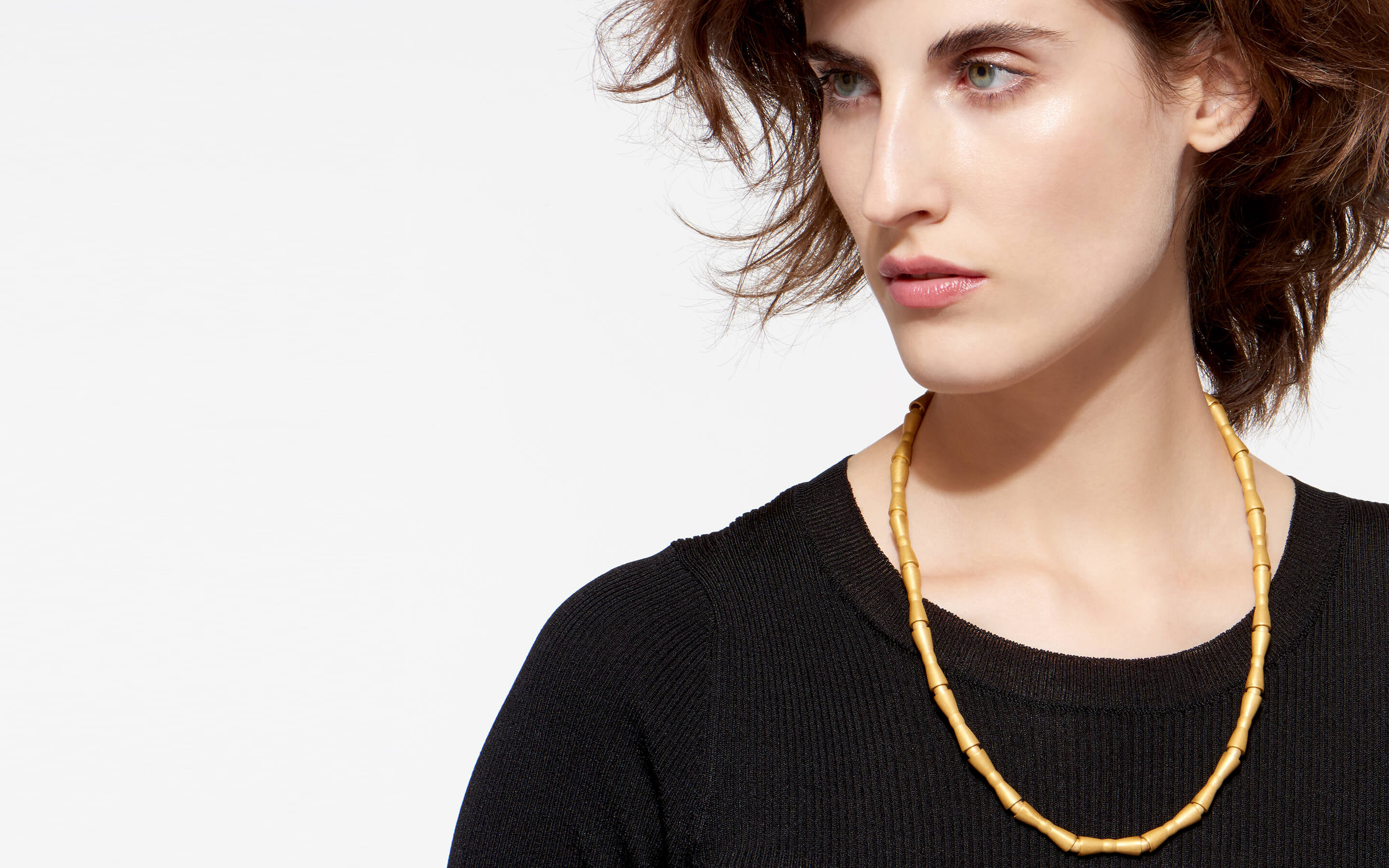 striking woman modeling 22 karat gold necklace containing long concave beads