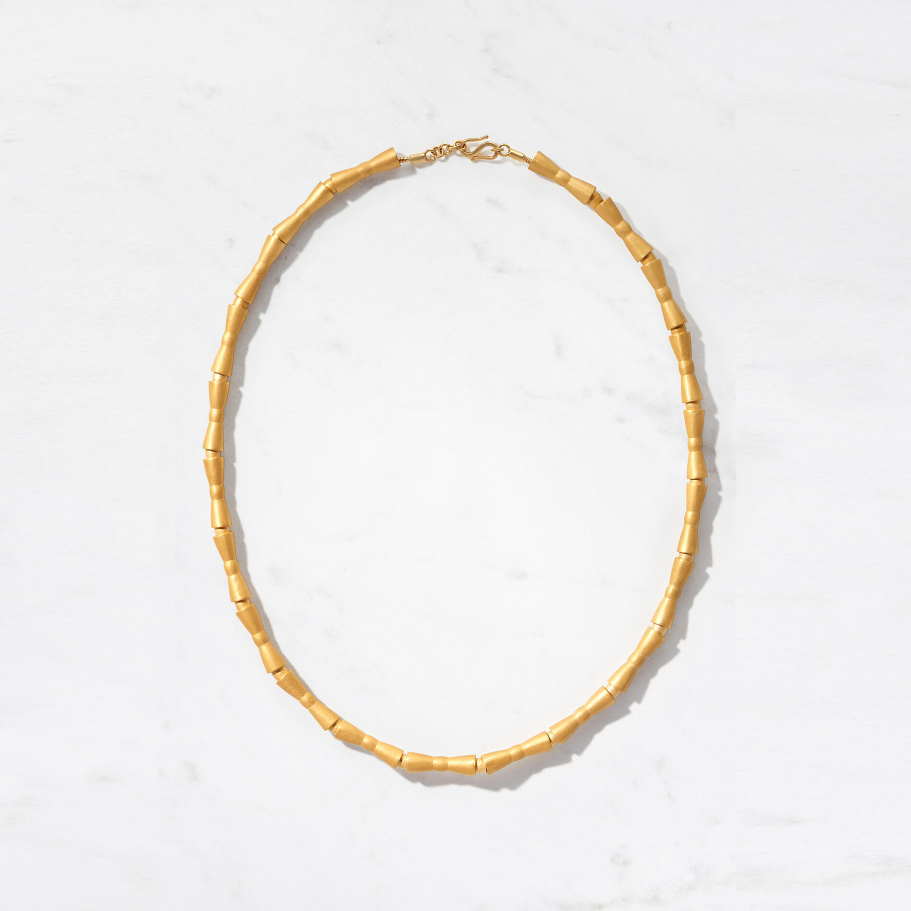 Adira Necklace transforms the concept of statement jewelry with linear, moveable beads carved from lustrous 22 karat matte gold. This piece, with a gold weight of 105 to 115 grams, is part of our Sculptura Collection. Available in two lengths.