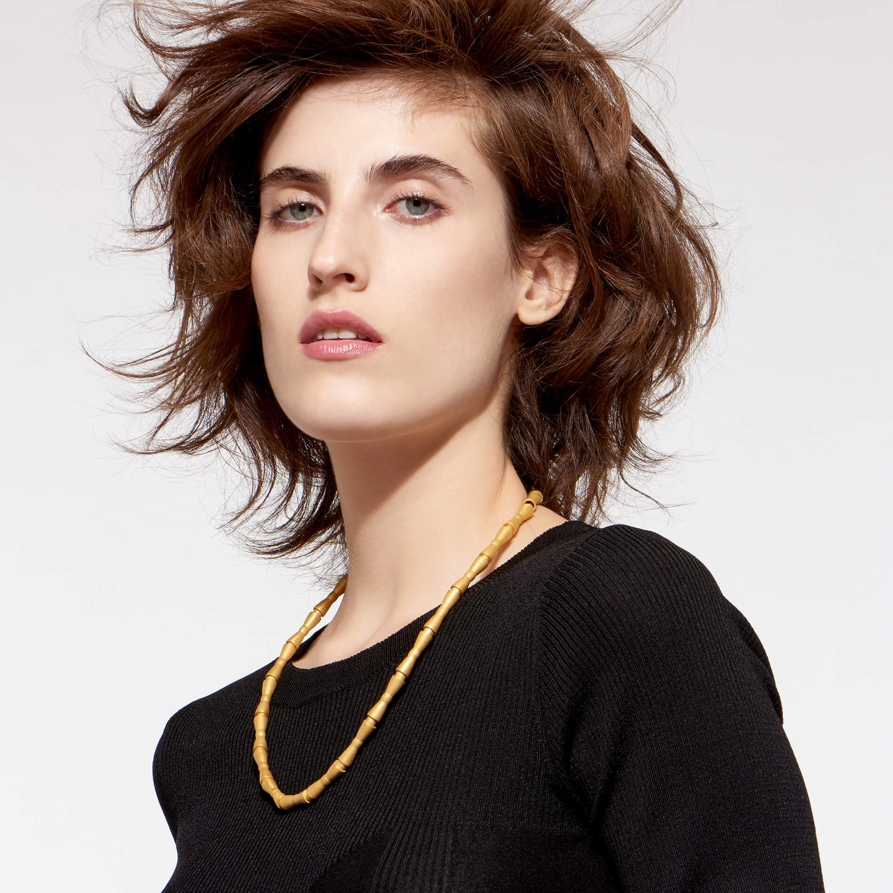 model with austere expression sporting 22 karat gold choker with bowtie-style beads in matte finish