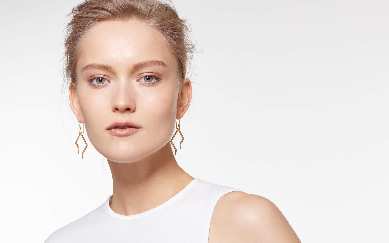alluring woman with 22 karat gold hook earrings in modern lightning design