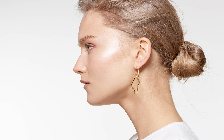 graceful model wearing 22 karat gold hook earrings designed as firebolts