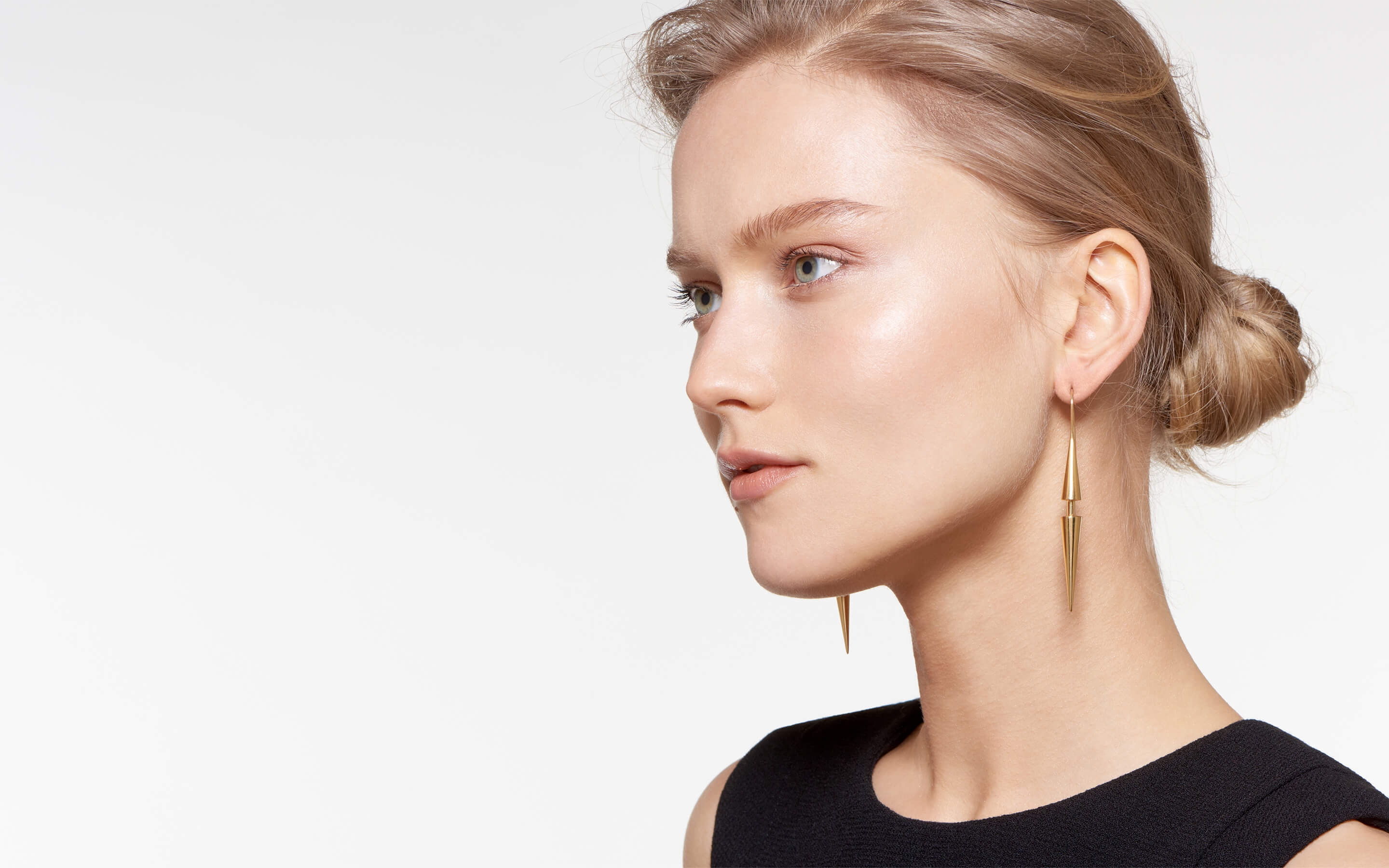 alluring model wearing shining earrings made of 22 karat gold cones