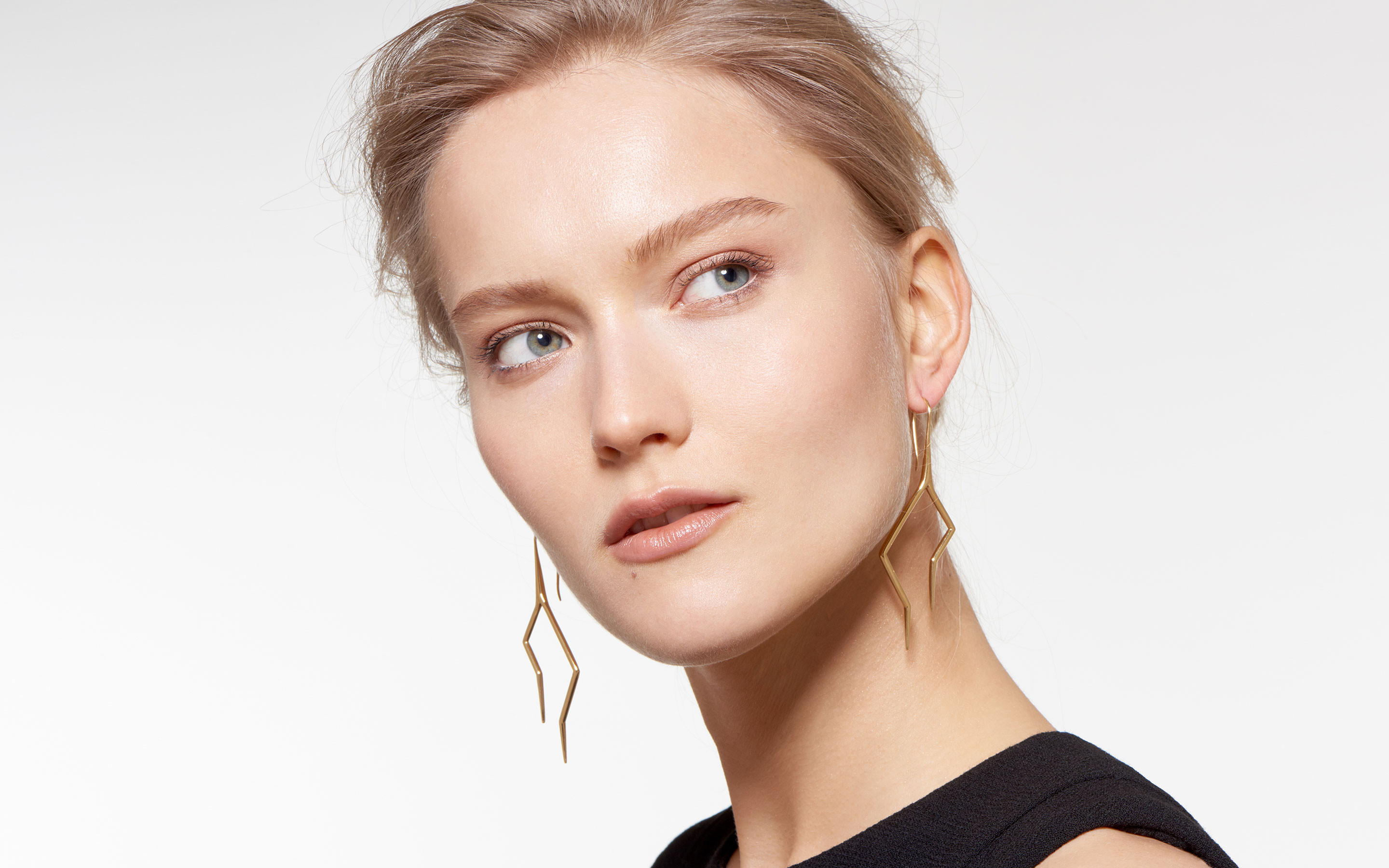 striking model adorned with 22 karat gold hook earrings in firebolt design