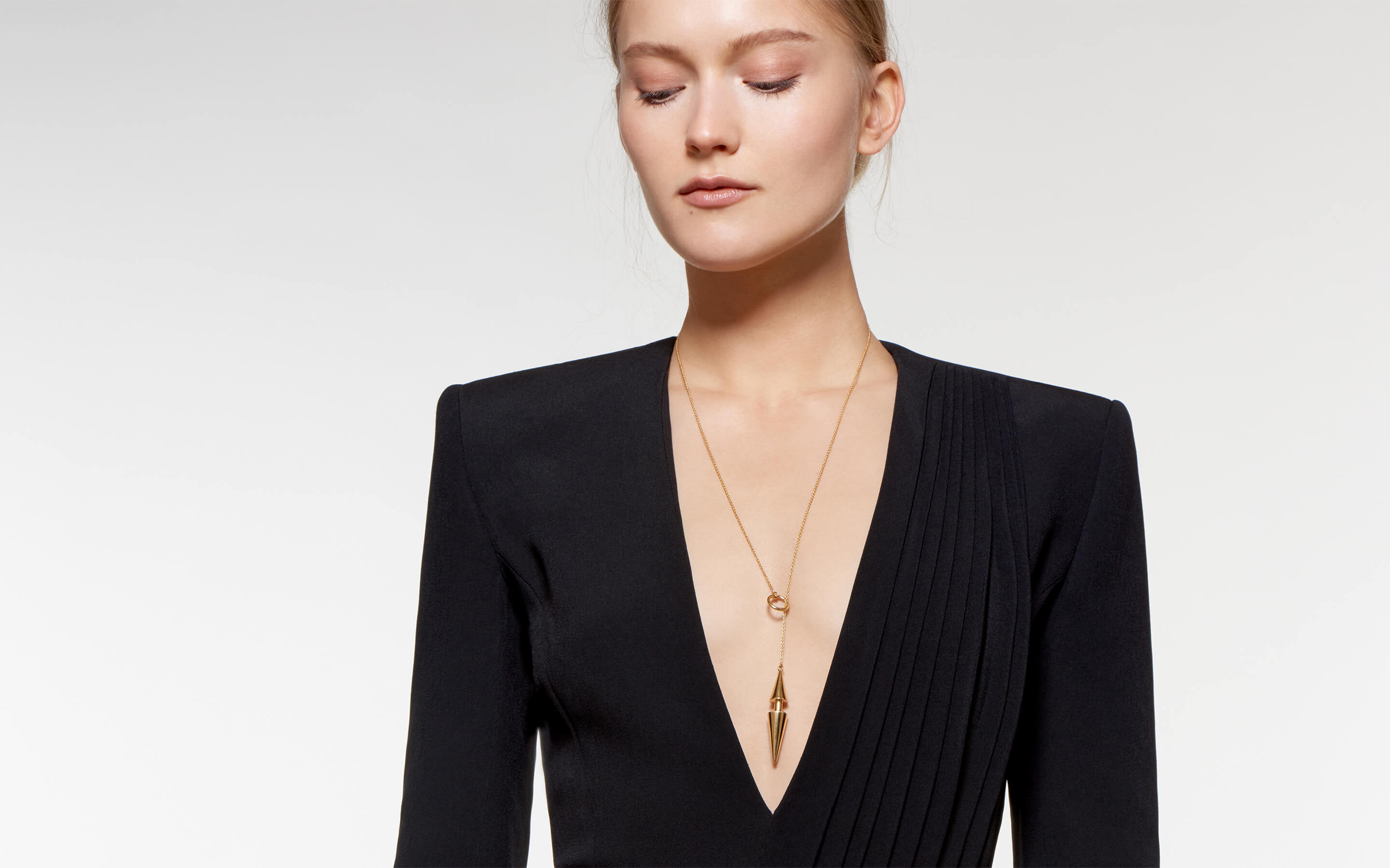 cool blonde model wearing 22 karat gold necklace in lariat-style with double cone pendant